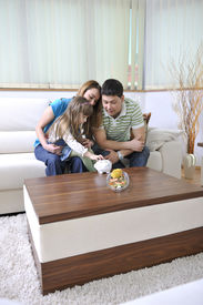 pic of save money  - young parent at home with beautiful child make savings and put coins money in piggy bank - JPG