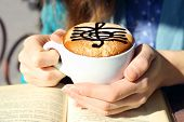 pic of clefs  - Hands holding cup of cappuccino with treble clef on foam - JPG