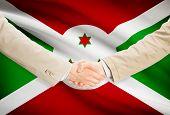 pic of burundi  - Businessmen shaking hands with flag on background  - JPG