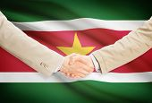 pic of suriname  - Businessmen shaking hands with flag on background  - JPG