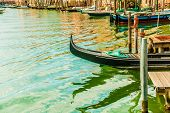 foto of gondola  - Beautiful colorful image of a canal in Venice with moorings and a gondola in the forefront and old houses under blue cloudy sky in the background - JPG