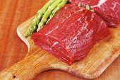 pic of veal  - red fresh raw beef veal fillet with asparagus on cutting plate over wooden table prepared to use - JPG