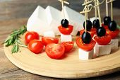 stock photo of canapes  - Cheese canapes with cherry tomatoes and olives on wooden tray close up - JPG