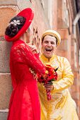 picture of fiance  - Laughing groom in traditional Vietnamese costume talking to his fiance - JPG