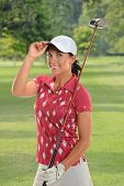 image of ladies golf  - Portrait of beautiful young golfer tipping cap on golf course - JPG