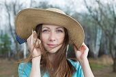 stock photo of windy  - Happy woman in hat listening seashell on a windy day - JPG