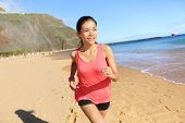 foto of biracial  - Running sports athlete runner woman on beach sweating and jogging - JPG