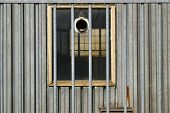 image of forlorn  - Vista through an industrial barrack window behind a fence - JPG