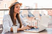 stock photo of funky  - Beautiful young woman in funky hat working on laptop and smiling while sitting outdoors - JPG