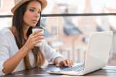 image of funky  - Beautiful young woman in funky hat working on laptop and smiling while sitting outdoors  - JPG