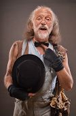 image of beggar  - Old homeless but cheerful beggar wearing jeans black gloves and hat - JPG
