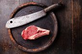 pic of meats  - Raw meat Ribeye steak entrecote and meat cleaver on dark background - JPG
