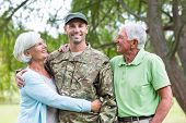 picture of reunited  - Soldier reunited with his parents on a sunny day - JPG