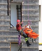 image of fireman  - fearless fireman during an exercise carries the stretcher with the climbing rope - JPG