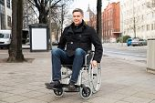 stock photo of disability  - Portrait Of A Smiling Disabled Man On Wheelchair In City - JPG
