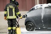 pic of firehouse  - two firefighters in action with foam to put out the fire of the car - JPG