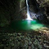 pic of penetration  - Hidden romantic waterfall flowing through a crevasse falling deep into a narrow gorge forming green lake lit by narrow sunray penetrating to the canyon - JPG