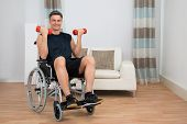 picture of handicap  - Handicapped Man On Wheelchair Working Out With Dumbbell At Home - JPG