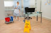 image of maids  - Young Maid Cleaning Floor With Mop In Office - JPG