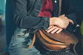 stock photo of clutch  - A young woman is sitting on a train and is clutching a handbag