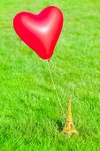 picture of bon voyage  - Miniature Eiffel tower at a meadow with a red heart shaped balloon tied on - JPG