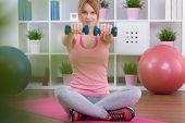 image of slender  - Slender pretty woman doing exercises with dumbbells - JPG