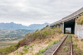 stock photo of passed out  - View of the old unused roalroad in Sir Lowrys Pass in the Hottentots - JPG