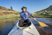 foto of horsetooth reservoir  - senior paddler in a decked expedition canoe on Horsetooth Reservoir - JPG
