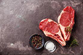 stock photo of slating  - Heart shape Raw fresh meat Ribeye Steak with rosemary pepper and salt on stone slate background - JPG