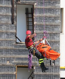 image of firemen  - fearless fireman during an exercise carries the stretcher with the climbing rope - JPG