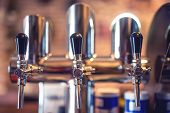 Beer Tap At Restaurant, Bar Or Pub. Close-up Details Of Beer Draft Taps In A Row poster