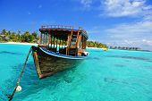 stock photo of dhoni  - Maldivian dhoni in front of the turquoise bay and island - JPG