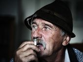 Closeup Artistic Photo of Aged Man With  Grey Mustache Smoking, grain added poster