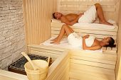 Couple lying in sauna wearing towel, relaxing with eyes closed.?