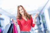Beautiful Happy Girl With Credit Card And Shopping Bags In Shopping Mall. Shopping Center In The Bac poster