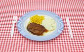 picture of frozen tv dinner  - Salisbury steak meal with corn and potato on a blue striped plate with plastic silverware on a red checkerboard cloth - JPG
