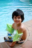 picture of floaties  - A young Hispanic boy plays by a luxurious pool - JPG