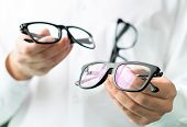 Optician Comparing Lenses Or Showing Customer Different Options In Spectacles. Eye Doctor Showing Ne poster