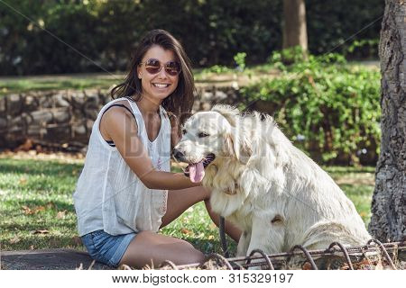 poster of Cheerful Young Dog Lover Sitting With The Dog In Summer Park. Beautiful Girl Wearing Stylish Sunglas