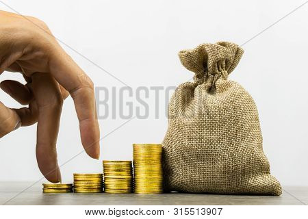 poster of Savings Money. Money Investment. A Businessman Hand On Stack Of Coins With Money Bag On Wood Table O