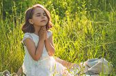 Little Girl Closed Her Eyes, Praying In A Field During Beautiful Sunset. Hands Folded In Prayer Conc poster