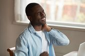 African Man Frowning Massaging Pinched Nerve Feels Pain In Neck poster