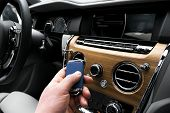 Mans Hand Holding A Wireless Ignition Car Key In White Leather Interior. Modern Car Interior Detail poster