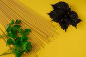 Spaghetti Sticks, Parsley And Sweet Basil Leaves On Yellow Kitchen Table Background. Food Photo For poster