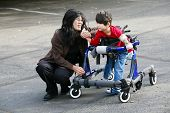 pic of physically handicapped  - Mother with disabled son walking outdoors with walker medical mobility equipment - JPG