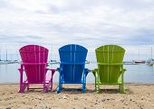 Multicoloured Muskoka Cottage Beach Chairs On The Sand Looking Out To The Harbor poster