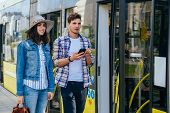 Stylish Couple Of Travelers Man And Woman With Backpacks Entering Tram At Outdoor Tram Stop. Group O poster