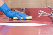 foto of house cleaning  - a worker is Cleaning red Bathroom Sink - JPG