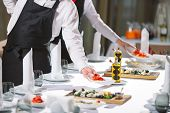 Waiter Serving Table In The Restaurant Preparing To Receive Guests. poster