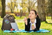 Blowing Soap Bubbles In The Wind. Close Up Shot Of A Beautiful Young Student Girl Lying On A Meadow  poster